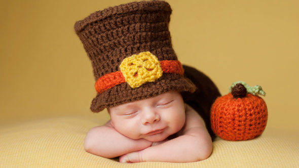 A sleeping Thanksgiving baby, cuddled up next to a knit pumpkin and wearing a brown pilgrim hat with an orange band.